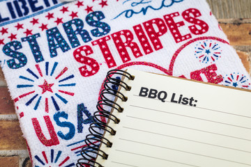 BBQ list concept on notebook and wooden board and Stars and Stripes banner for patriotic themed event