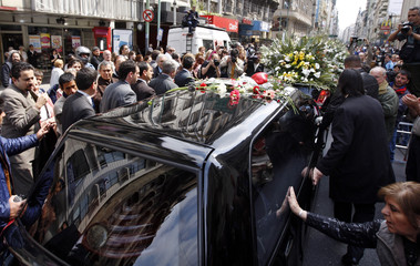 People line the street to bid farewell as the hearse carrying the coffin of deceased folk singer Mercedes Sosa moves from the Congress to the cemetery in Buenos Aires