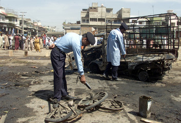 BOMB DISPOSABLE EXPERT EXAMINES THE SITE OF A BOMB EXPLOSION IN ISLAMABAD.