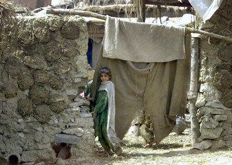 An Afghan child stands outside her mud house at a village where many Afghan refugees live in Islamab..