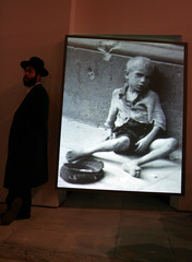 An ultra-Orthodox Jewish visitor stands alongside a photograph of a starving child during a visit to ...