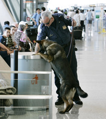 Police officer and his bomb sniffing dog check trash container at Dulles Airport outside Washington