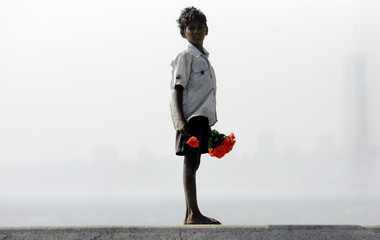 A young hawker selling roses waits for customers at a waterfront on Valentine's Day in Mumbai
