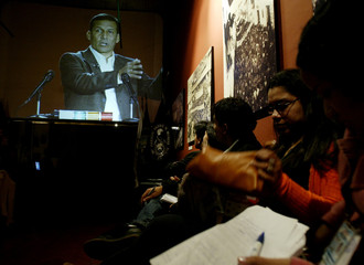 Journalists watch Peruvian presidential candidate Humala on screen during TV presidential debate in Lima