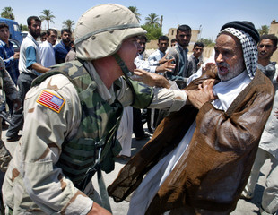 A U.S. military policeman pushes an Iraqi man during a demonstration July 27, 2003 in the city of Ke..