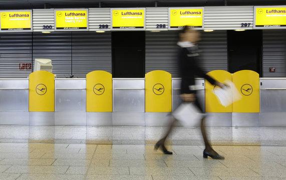 Employee walks in front of empty check-in desks in the departure hall at Frankfurt airport