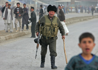 Afghan policeman walks after a protest against cartoons of the Prophet Mohammad on the outskirts of Kabul