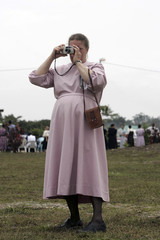 A Mennonite woman takes a picture at a parade in Belize