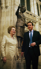 Former British PM Thatcher and current leader of the Conservative Party Cameron stand in front of a bronze statue of Thatcher inside the Palace of Westminster