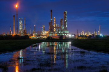Oil refinery or petroleum refinery industry landscape with reflection at twilight time in the morning. Industrial estate of Thailand, industrial process plant where crude oil is processed and refined.