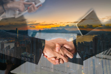 Double Exposure of a businessman handshake on Aerial view of Sunrise over Victoria Harbor as viewed atop Victoria Peak