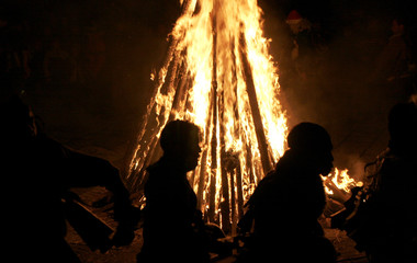 Bulgarian men dressed in animal costumes dance in front of a ritual bonfire during a festival in Yazhdrilovtsi