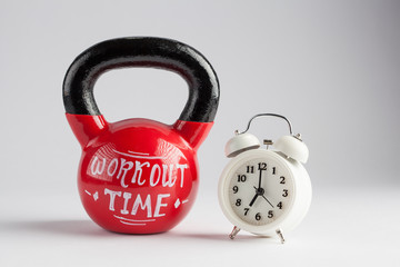 Red kettlebell with Workout Time lettering written on it and traditional alarm clock isolated on white with copy space. Time to work out, healthy lifestyle concept