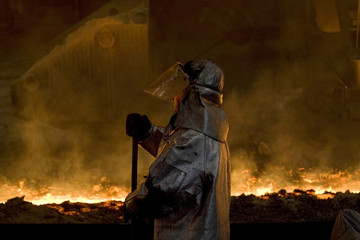 A foundry hand controls a flow of liquid iron in a steel-foundry of the largest steelworks of the Czech Republic Mittal Steel Ostrava