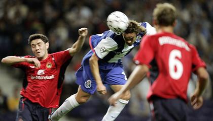 Porto's Adriano jumps for the ball next to CSK Moskva's Ignashevich and Berezutski in Porto