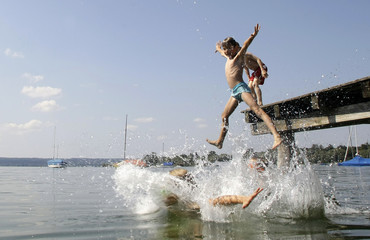 Young boys jump into lake Ammersee on a hot day in Herrsching