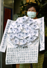 MOURNER CARRIES WREATH TO DOCTOR'S FUNERAL WHO DIED FROM SARSIN HONG KONG.