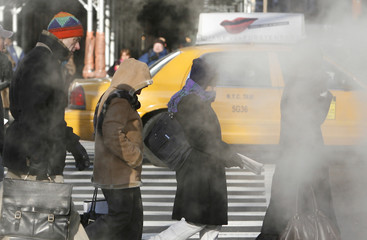 Morning commuters walk through steam from a drain pipe during the morning rush in New York