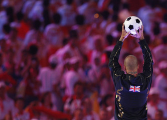 Soccer player David Beckham holds a soccer ball before kicking it during the closing ceremony of the Beijing 2008 Olympic Games at the National Stadium
