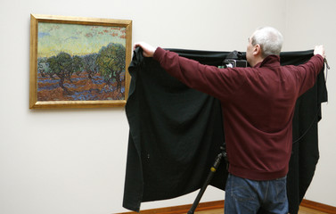 A photographer uses a black cloth as he takes a picture of 'Olive-grove, Saint Remy'  by van Gogh at the Kunstmuseum Basel in Basel