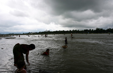 Indian labourers collect stones in the Balason river on the outskirts of the north-eastern city of Siliguri