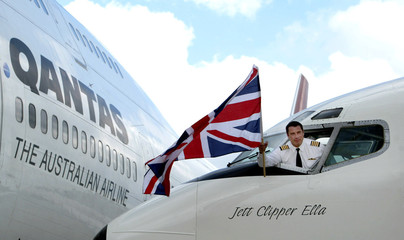 U.S. actor John Travolta waves a Union flag from the cockpit of his vintage Boeing 707 jet aircraft ..