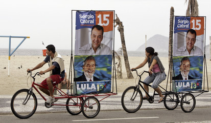 People ride their bikes with posters of Brazil's President Lula and Rio's Governor candidate Cabral at Copacabana beach in Rio de Janeiro