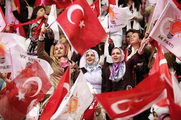 Turkey's ruling AKP supporters cheer and wave national and party flags as their leader PM Erdogan enters the hall in Ankara