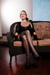 Older Woman Sitting In Black Lingerie And Stockings