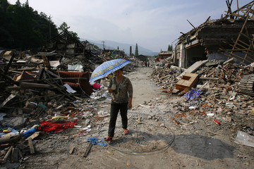 Woman walks past collapsed buildings in the earthquake-hit area of Shang Er, Sichuan province