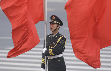 A soldier holding a red flag stands during a welcoming ceremony in Beijing