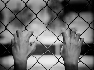 Black and white of Women Hands holding fence on outdoor scenery during daylight. Hand In Jail, concept of life imprisonment