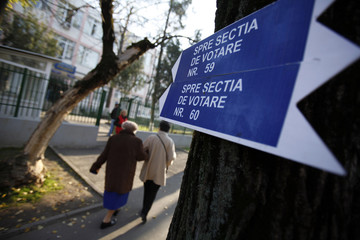 A sign points to a polling station as people arrive to vote in Bucharest