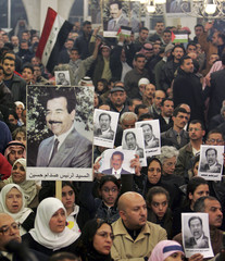 Jordanian demonstrators hold pictures of former Iraqi President Saddam during a protest against his execution in Amman