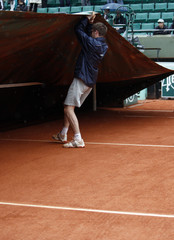A maintenance worker covers the court as it rains during the French Open tennis tournament at Roland Garros stadium in Paris