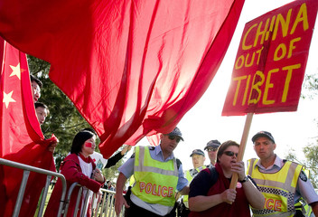 A pro-Tibet supporter is escorted away from pro-China supporters during the Olympic torch relay in Canberra
