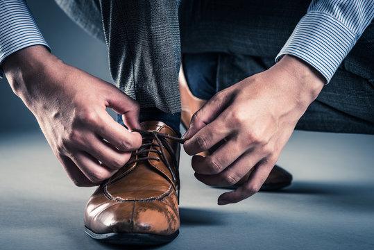 革靴の紐を結ぶ男性
