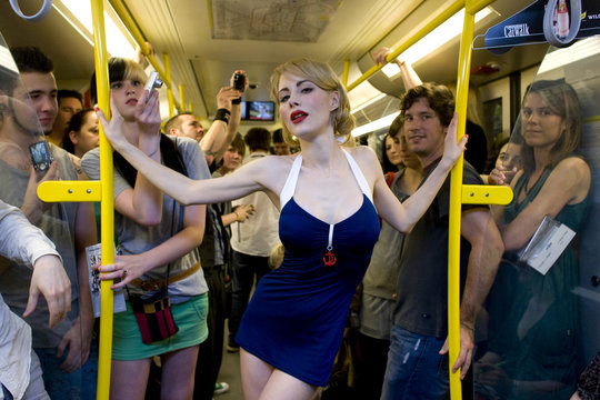 A model presents a creation by Pinup Couture during a fashion show in an underground train in Berlin