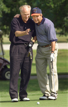 BUSH GETS HELP READING A PUTT AS HE PLAYS A ROUND OF GOLF AT ANDREWS.