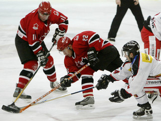SWITZERLANDS GUIGNARD FIGHTS FOR PUCK WITH CANADA'S ROEST AND INLOTO CUP IN SLOVAKIA.