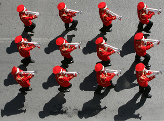 Trumpeters of a school band blow their instruments as thousands of youths attend a march through a main street in Istanbul