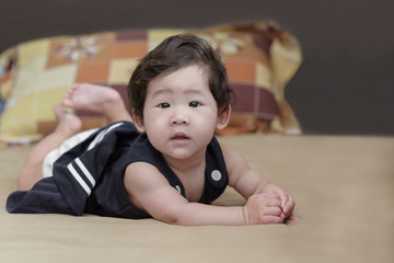 Adorable asian baby girl lying on bed.