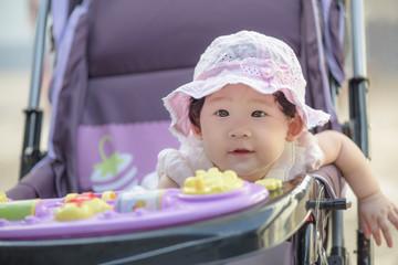 Portrait of sweet little asian baby girl sitting in stroller.