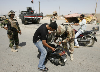 An Iraqi soldier searches the trunk of a scooter at a checkpoint in Baghdad's Sadr City