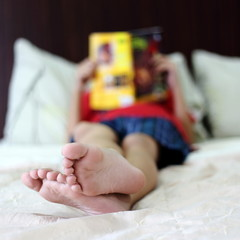 Unidentified Boy Reading Book on Bed