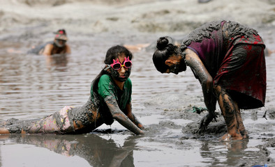Women covered with mud enjoy medicinal lagoon in Chilca.