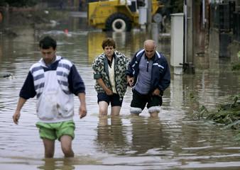 A Bulgarian family walks through a flooded street in Elin Pelin.