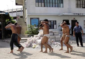 Members of Abu Sayyaf Muslim rebels walk half-naked after they surrender to the police inside ...