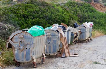 Four overloaded wheeled trashbins