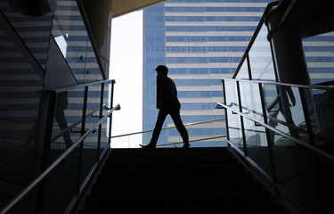 A businessman walks past an office building in Tokyo